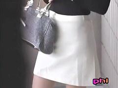 Slim Asian chick texting gets a good skirt sharking.