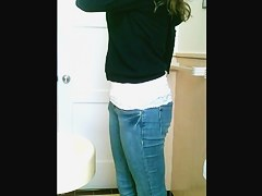 A jeans wearing girl is peeing in the bathroom